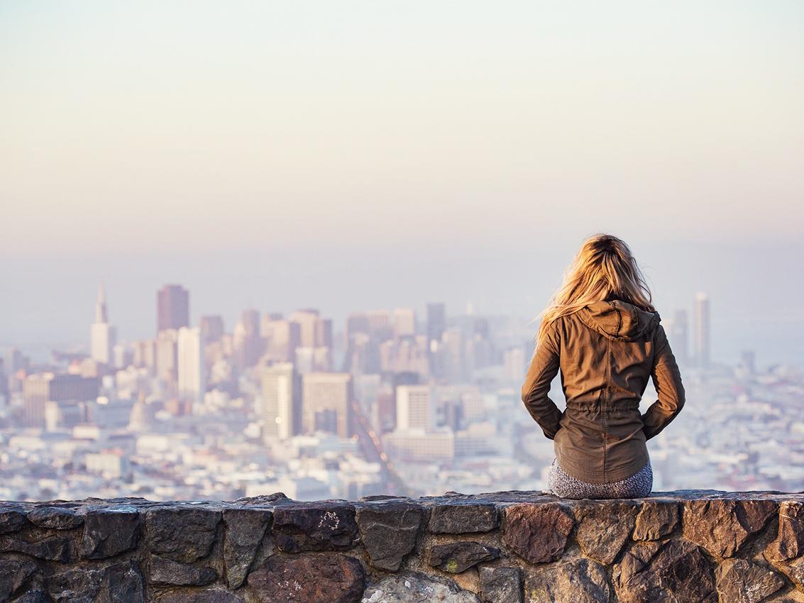 Mulher sozinha olhando a cidade