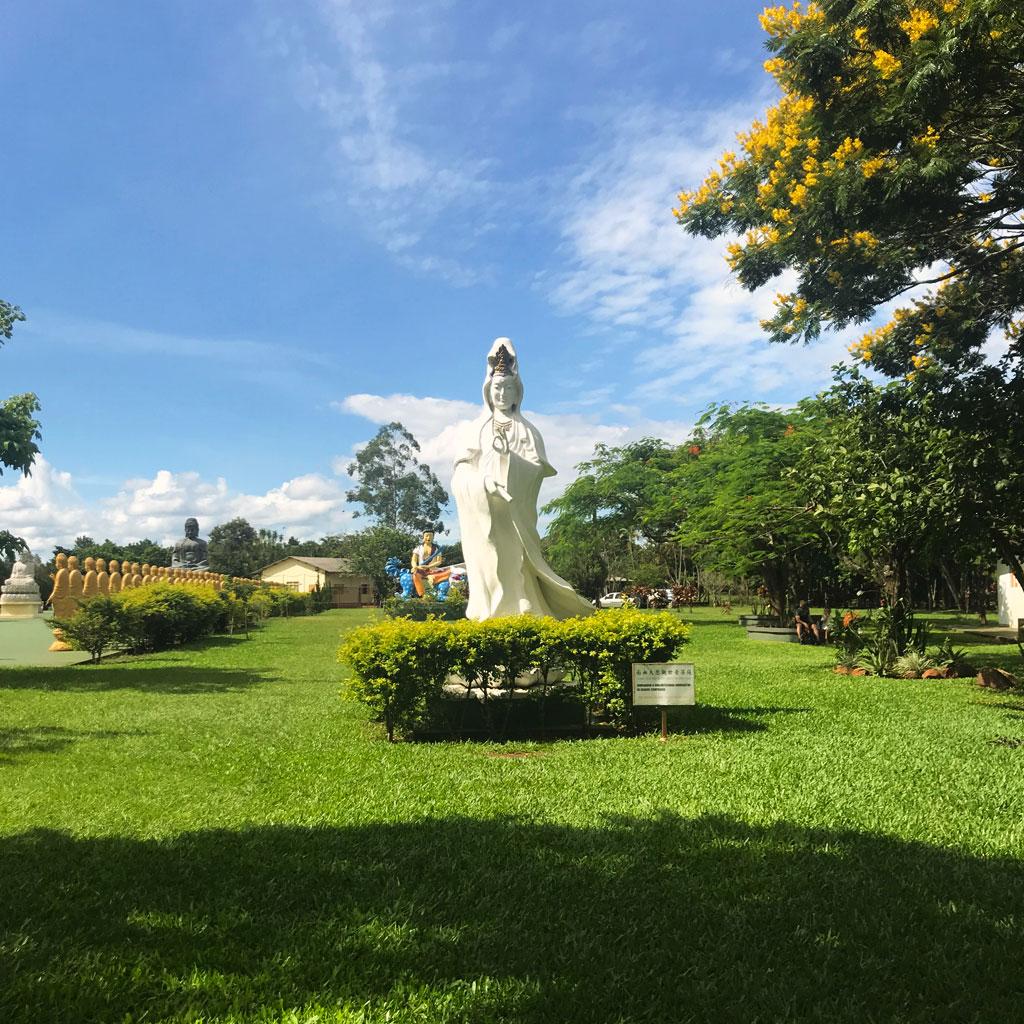 Conhecendo os jardins do templo Budista - estátua linda na entrada